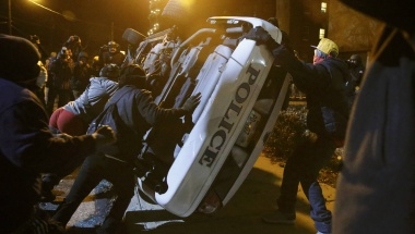 Protesters flip over a Ferguson police car in Ferguson, Missouri, November 25, 2014. REUTERS/Jim Young