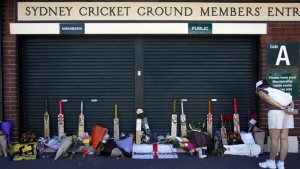 A woman reads messages as she looks at tributes left to Australian cricketer Phillip Hughes, who died on Thursday, placed at the main gates to the Sydney Cricket Ground (SCG) November 29, 2014.  REUTERS/David Gray