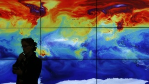 A participant is pictured in front of a screen projecting a world map during the World Climate Change Conference 2015 (COP21) at Le Bourget, near Paris, France, December 8, 2015. REUTERS/Stephane Mahe