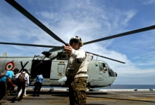 A U.S. Marines Corps personnel guides the media on board the USS Boxer LHD as a helicopter prepares for takeoff at a location off Goa in this October 29, 2006 file photo.    REUTERS/Prashanth Vishwanathan/Files
