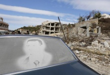 An image of Syria's President Bashar al-Assad is seen on a car parked in front of damaged buildings in the town of Rabiya, after pro-government forces recaptured the rebel-held town in coastal Latakia province, Syria January 27, 2016. REUTERS/Omar Sanadiki