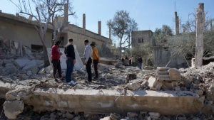 People inspect the damage after airstrikes by pro-Syrian government forces in the rebel held town of Dael, in Deraa Governorate, Syria February 12, 2016. REUTERS/Alaa Al-Faqir