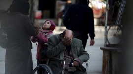 A girl asks a passerby for help to pay a medical bill as her father sits in his wheelchair in the Douma neighbourhood of Damascus Syria February 3, 2016.  REUTERS/Bassam Khabieh