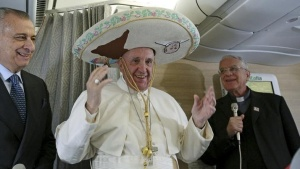 Pope Francis wears a Sombrero hat he received as a gift by a Mexican journalist aboard an airplane to Havana, February 12, 2016.  REUTERS/Alessandro Di Meo/Pool