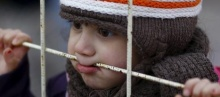 A Syrian boy looks through a gate as others wait to cross into Syria at Oncupinar border crossing in the southeastern city of Kilis, Turkey February 11, 2016.  REUTERS/Osman Orsal