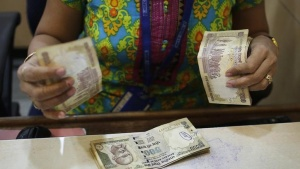 A cashier counts Indian rupee currency notes inside a bank in Mumbai December 6, 2013.  REUTERS/Danish Siddiqui/Files
