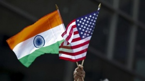 A man holds the flags of India and the U.S. while people take part in the 35th India Day Parade in New York August 16, 2015. REUTERS/Eduardo Munoz/Files