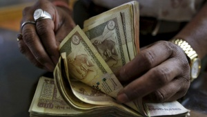 A money lender counts rupee notes at his shop in Ahmedabad, in this May 6, 2015 file photo. REUTERS/Amit Dave/Files