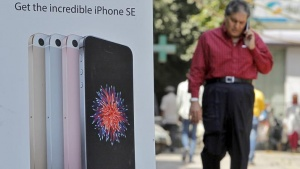 A man speaks on his mobile phone as he walks past an Apple iPhone SE advertisement billboard in a street in New Delhi, India, April 25, 2016. REUTERS/Anindito Mukherjee/Files