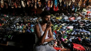 A shopkeeper drinks tea as he waits for customers at his roadside footwear stall in Kolkata, India May 30, 2016. REUTERS/Rupak De Chowdhuri