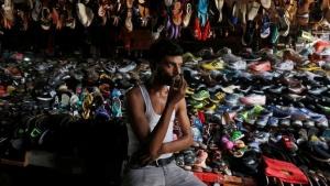 A shopkeeper drinks tea as he waits for customers at his roadside footwear stall in Kolkata, India May 30, 2016. REUTERS/Rupak De Chowdhuri