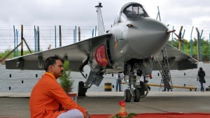 A Hindu priest waits to perform prayers next to Tejas, India's first locally-built Light Combat Aircraft (LCA), before its induction into the Indian Air Force at the Hindustan Aeronautics Limited (HAL) Airport in Bengaluru, July 1, 2016. REUTERS/Abhishek N. Chinnappa