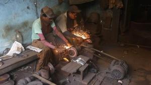 Workers sharpen scissors inside a workshop in Kolkata, India, June 9, 2016. REUTERS/Rupak De Chowdhuri