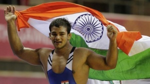 India's Narsingh Pancham Yadav holds his national flag as he celebrates winning the gold medal in the 74kg men's freestyle wrestling match at the Commonwealth Games in New Delhi October 9, 2010. REUTERS/Krishnendu Halder/Files