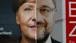 A combination photo shows a defaced election campaign poster of the Christian Democratic Union (CDU) party, with a headshot of German Chancellor Angela Merkel and Social Democratic Party (SPD) top candidate Martin Schulz in Frankfurt, Germany, September 20, 2017. REUTERS/Kai Pfaffenbach
