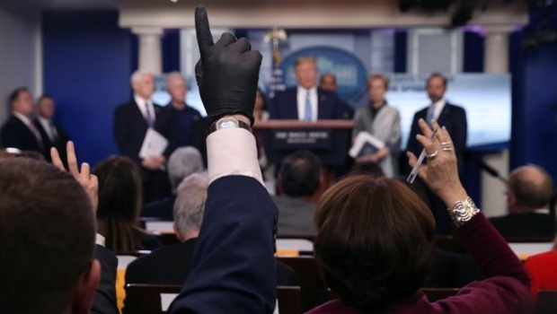 A reporter wears a latex glove while trying to ask a question of U.S. President Donald Trump during a news briefing on the coronavirus (COVID-19) at the White House in Washington, U.S., March 16, 2020. REUTERS/Leah Millis