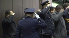 NYPD officers salute their fallen comrades