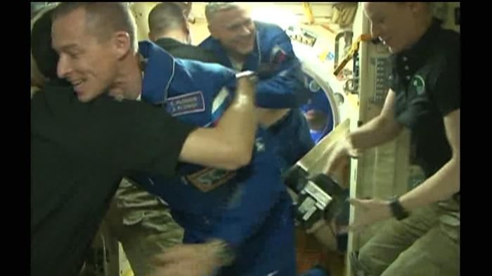 Hugs, handshakes as hatch opens at ISS