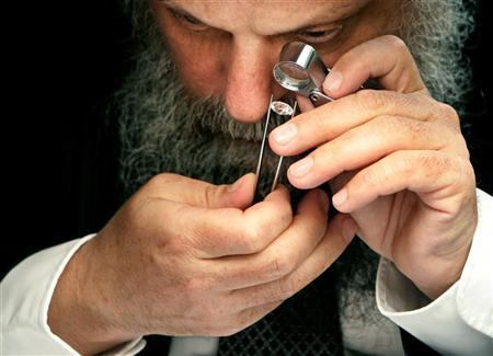 A diamond dealer checks the quality of a diamond in a file photo. Diamond merchants form an enclave along a western block of Manhattan's 47th Street that is lined with jewelry stores. The Diamond Dealers Club estimates some 2,000 businesses along the street are connected in some way to the diamond businesses, among them shops, dealers and gem cutters. Many who work there are ultra-Orthodox Jews, clad in traditional long dark coats, black hats and beards. REUTERS/Francois Lenoir