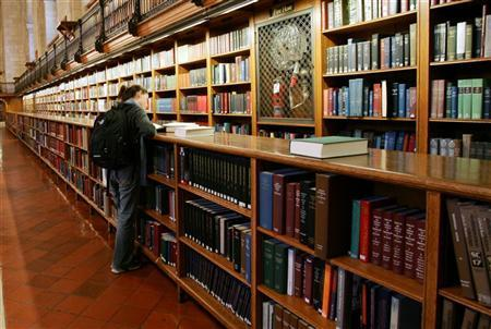 A woman stands among the bookshelves in the main reading room of The New York Public Library, December 14, 2004. A U.S. appeals court has rejected a bid by Internet activists to roll back federal laws that extended copyright protection over orphan works, or books and other media that are no longer in print. REUTERS/Mike Segar