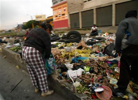 A file photo of a couple sifting through the garbage for food in Guatemala City September 13, 2005. Director Leslie Iwerks filmed at the dump in Guatemala City, Central America's largest garbage dump, for four years to make ''Recycled Life,'' nominated for an Oscar for best documentary short. REUTERS/Daniel LeClair