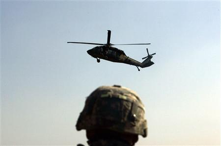 A U.S. soldier watches the landing of a Blackhawk helicopter at forward operating base Loyalty in Baghdad, February 8, 2007. REUTERS/Carlos Barria