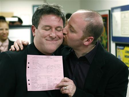 Daniel Gross (R) kisses his partner, Steven Goldstein, who is holding a New Jersey civil union certificate, after the completion of their civil union ceremony at the offices of State Senator Loretta Weinberg in Teaneck, New Jersey, February 19, 2007. REUTERS/Jeff Zelevansky