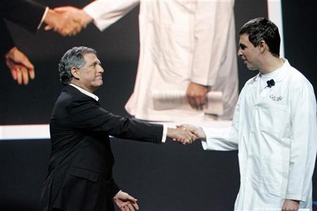 CBS Chief Executive Leslie Moonves (L) shakes hands with Google co-founder Larry Page at the Consumer Electronics Show in Las Vegas, Nevada January 6, 2006. A deal between Google and CBS that would let YouTube users watch clips from CBS shows has unraveled, the Wall Street Journal reported on Wednesday. REUTERS/Steve Marcus