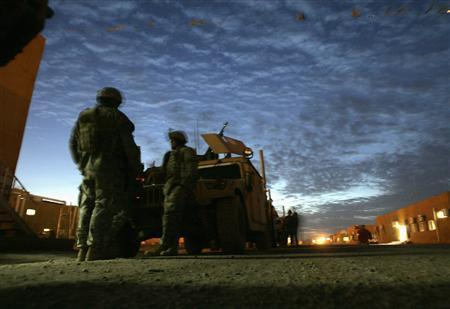 U.S. soldiers wait before an early patrol southeast of Baghdad February 22, 2007. REUTERS/Carlos Barria