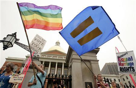 Demonstrators wave flags in support of gay marriage in front of the Massachusetts State House in Boston, Massachusetts, in this July 12, 2006 file photo. A federal judge in Boston has dismissed a suit by two families who wanted to stop a Massachusetts town and its public school system from teaching their children about gay marriage, court documents show. REUTERS/Jessica Rinaldi/Files