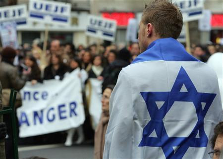 In this file photo a man draped an Israeli flag takes part in a march through Paris attended by thousands of people to protest against racism and anti-Semitism following the torture and killing of a young Jewish victim, February 26, 2006. REUTERS/Regis Duvignau