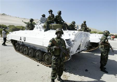 Ugandan soldiers stand guard next to a U.N. armoured personnel carrier in Mogadishu's international airport, March 6, 2007. REUTERS/Shabelle Media