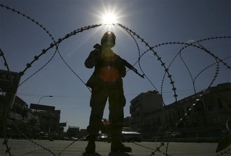 An Iraqi soldier stands guard behind barbed wire at a checkpoint in Baghdad, March 10, 2007. REUTERS/Ceerwan Aziz