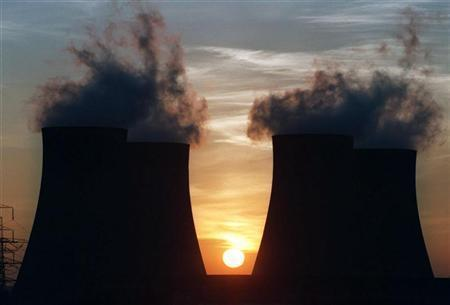 The sun is seen setting behind the cooling towers of the Ratcliffe-on-Soar power station in a file photo. The government will publish a climate change bill on Tuesday which will set targets for carbon dioxide emissions cuts and could make the country the first to limit greenhouse gases by law. REUTERS/Dennis Owen