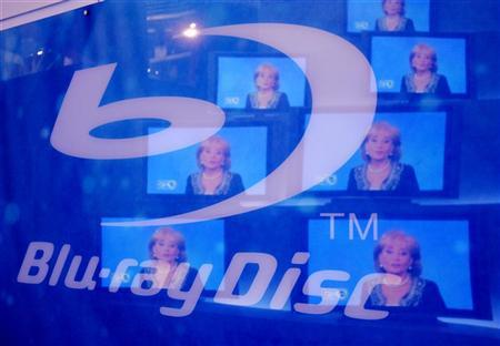 Television images are reflected on a sign for Blu-ray Discs at the 2007 International Consumer Electronics Show (CES) in Las Vegas, Nevada January 9, 2007. The Blu-ray disc association said on Thursday it aimed to become replace the DVD media storage format within three years. REUTERS/Rick Wilking