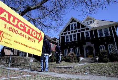 An auction lawn sign points to a foreclosed property to be auctioned off by Dallas-based Hudson & Marshall along with several hundred other foreclosed homes in Detroit, Michigan March 18, 2007. Job losses in the U.S. industrial heartland have left states like Michigan and Ohio more vulnerable to mortgage defaults, as home finance costs rise amid often moribund real-estate markets. REUTERS/Rebecca Cook