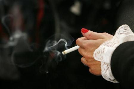 A woman smokes in this February 7, 2007 file photo. Smoking not only can wrinkle the face and turn it yellow -- it can do the same to the whole body, researchers reported on Monday. REUTERS/Lucas Jackson
