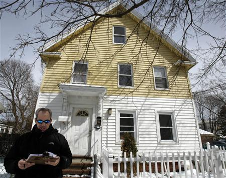 An auctioneer reads a public notice before taking bids on a foreclosed home (rear) in Lynn, Massachusetts March 19, 2007. REUTERS/Brian Snyder