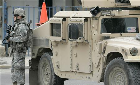 A U.S. soldier stands guard near an armoured vehicle at a checkpoint in Baghdad March 24, 2007. REUTERS/Namir Noor-Eldeen