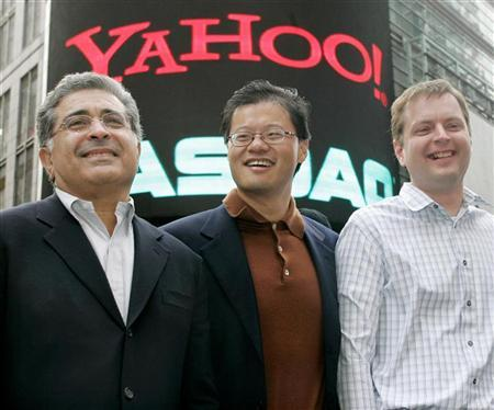 Yahoo! co-founders Jerry Yang (C) and David Filo (R) pose with chief executive Terry Semel in front of the NASDAQ MarketSite in Times Square in New York after ringing the opening bell at NASDAQ in this March 2, 2005 file photo. Yahoo will offer international news from reporters working with U.S. newspaper publisher McClatchy Co., including a blog written by Iraqi staffers, the companies said on Wednesday. REUTERS/Peter Morgan PM