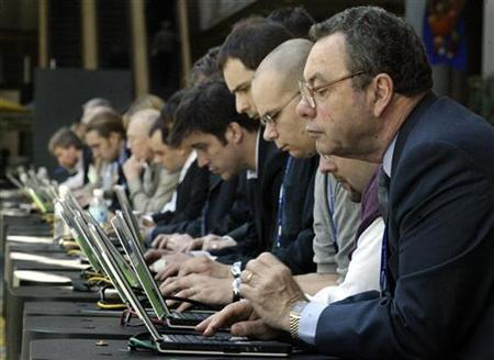 People are seen using wireless computers during a trade show in Atlanta, Georgia March 24, 2004. People who use the Internet to read the news have a greater attention span than print readers, according to a U.S. study that refutes the idea that Web surfers jump around and don't read much. REUTERS/Tami Chappell