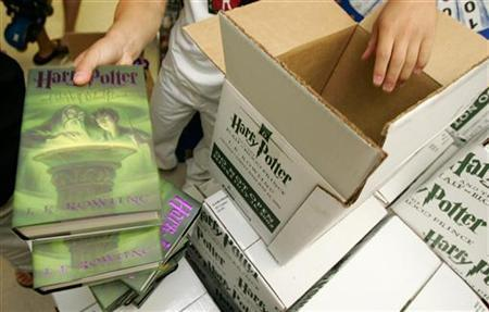 Saunder Yipp unpacks a box of ''Harry Potter and the Half-Blood Prince'', by J.K. Rowling, at midnight in the Magic Tree Bookstore in Oak Park, Illinois, a Chicago suburb, July 16, 2005. Harry Potter publisher Bloomsbury said on Monday it had begun working with digital book company LibreDigital to let readers search and preview book content via the Web. REUTERS/John Gress