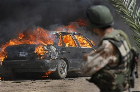 An Iraqi soldier watches a car burn during a joint operation with U.S. Army soldiers near Mahmudiya, south of Baghdad April 16, 2007. REUTERS/Bob Strong
