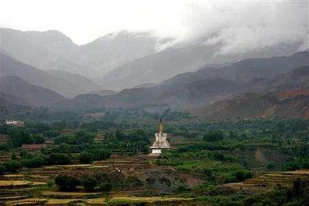 A Tibetan stupa is seen at the foot of a mountain in Xionghua County, northwestern China's Qinghai province August 17, 2006. China has created artificial snow for the first time in Tibet, Xinhua news agency reported on Wednesday, months after experts warned of melting glaciers and drought in the Himalayan region. REUTERS/Jason Lee