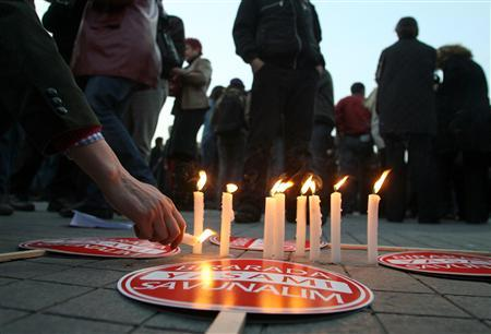 A protester lights a candle during a demonstration in Istanbul April 18, 2007, against an attack on a publishing house in Turkey's southeastern province of Malatya. REUTERS/Osman Orsal