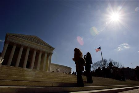 Tourists take photos of the U.S. Supreme Court in Washington in this February 21, 2006 file photo. The Court's ruling last week that outlawed a certain abortion procedure could be a first step of greater government intrusion into private medical decisions, doctors said on Monday. REUTERS/Kevin Lamarque