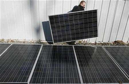Engineer homeowner Mike Strizki carries a solar panel past an array of panels at the shop next to his residence in Hopewell, New Jersey, January 4, 2007. ''Eco-friendly'' is the buzz-word of the 21st century and the environmental conscience is increasingly determining decisions on the British home front. REUTERS/Tim Shaffer