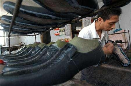 A file photo of a shoe maker working at a workshop in Xiangfan, central China's Hubei province July 5, 2006. REUTERS/Stringer
