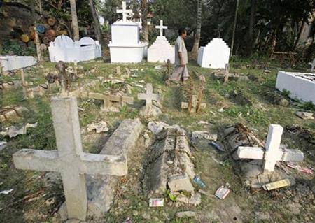A man walks inside a graveyard in Indian city of Kolkata November 27, 2006. A villager is campaigning in northern India for the rights of people declared legally dead by cheating relatives seeking to steal their assets. REUTERS/Parth Sanyal