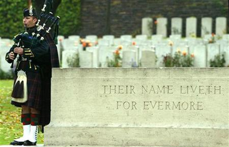 The Highlander's regimental piper plays during the re-buriel of two Scottish soldiers killed in WWI, October 20, 2004. More people now visit Commonwealth war graves around the world than at any time in the past 90 years and writer Julie Summers thinks she knows why. REUTERS/Pascal Rossignol PR/AA